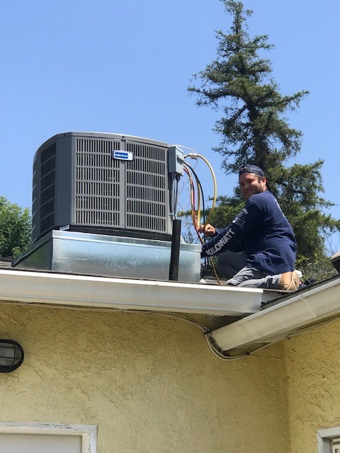 Kilowatt AC Service technician with rooftop compressor